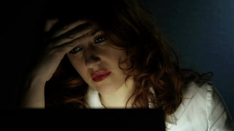 young attractive woman sat at her desk working in a dark room Footage