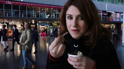 woman eating a cup of ice cream with train station life in background Footage