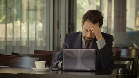 depressed businessman sitting and working in a cafè: problems, troubled Footage