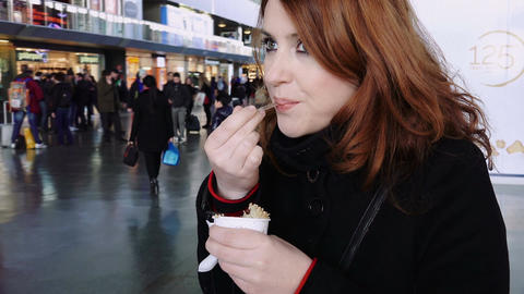 woman eating an icecream inside a train station while waiting the train Footage