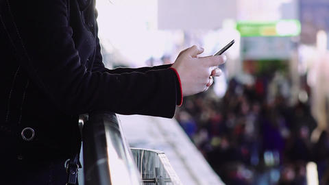 woman's hands using smartphone to text a message with crowd in background Footage