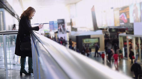 young woman using a mobile phone to send a message in a train station Footage