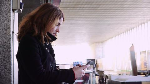 young woman sending messages inside a train station using her smartphone Footage