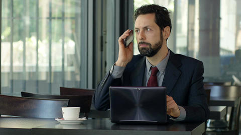 angry businessman sitting alone with laptop and mobile phone Footage
