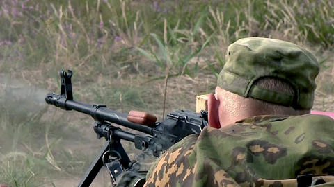 A military soldier in camouflage shoots lying in the grass with a machine gun Live Action