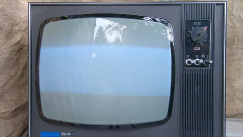 Old TV is turned on by hand. Glowing Retro TV Screen Flickers On and Off. Retro background fabric Live Action