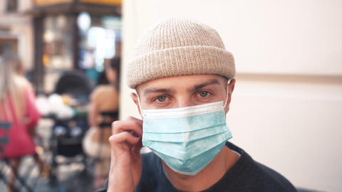 Close up of face of young handsome Caucasian man taking off medical mask at cafe Live Action