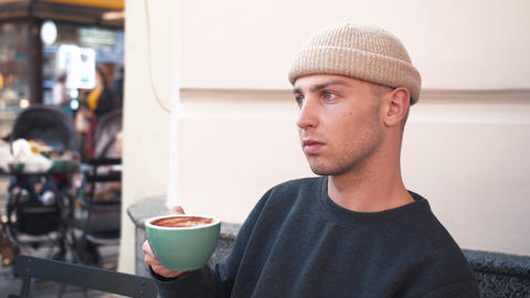 A closeup portrait of an attractive young caucasian man holding coffe cup at Live Action