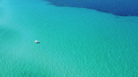 Boat sailing on turquoise crystal clear sea water in summer sunny day on exotic destination. Aerial Live Action