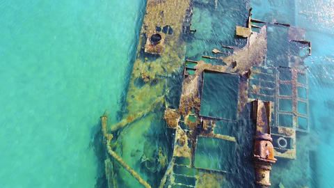 Close up of tranquil turquoise sea and old abandoned stranded ship in the sea. Light wind moving sea Live Action