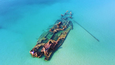 Abandoned old stranded ship in turquoise clear sea. Aerial view of ship wreck lying in the sea after Live Action