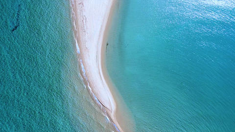 Tropic sandbank beach top view and turquoise crystal clear sea splashing the beach Live Action