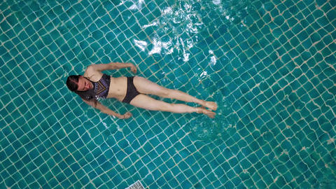 Young woman swimming in open green swimming pool. Outdoor activities. Healthy Live Action