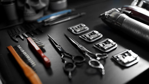 Stylish equipment table with scissors and trimmers and dark scull at the barber shop Live Action