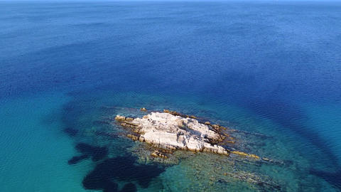 Exotic big rock in the middle of the blue clear and tranquil sea. Aerial view Exotic big rock in the Live Action