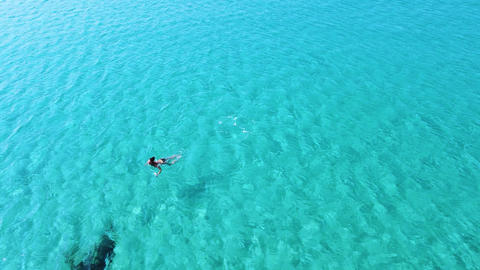 Aerial view of one young woman swimming alone in empty clean turquoise sea Live Action