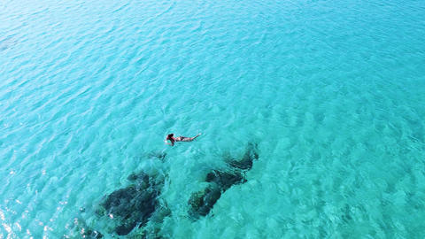 Aerial view of one young woman swimming alone in empty clean turquoise sea Aerial view of one young Live Action