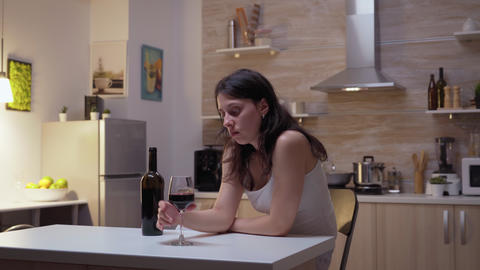 Sad wife drinking in the kitchen Live Action