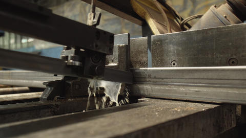 Coolant splashes fall on surface of metal during sawing on metalworking machine Live Action