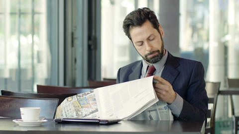 businessman reading newspaper sitting in a cafeteria Footage