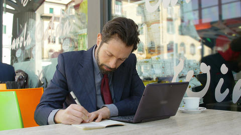 businessman at work with laptop and notepad: businessman working in a coffee sh Footage