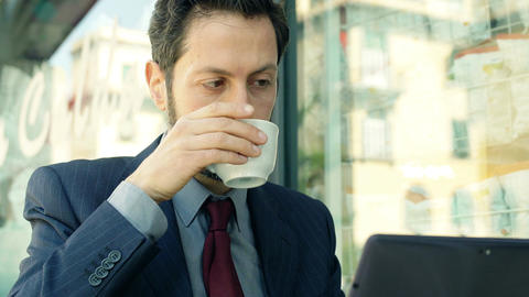 businessman using a laptop and working out of his office sitting in a cafè Footage