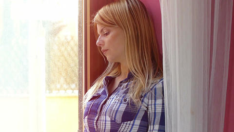 sad woman at the window looking out to remember someone that's gone away Footage