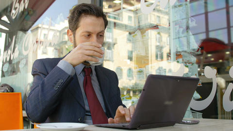 businessman at work and drinking coffee: working in a cafeteria with laptop Footage