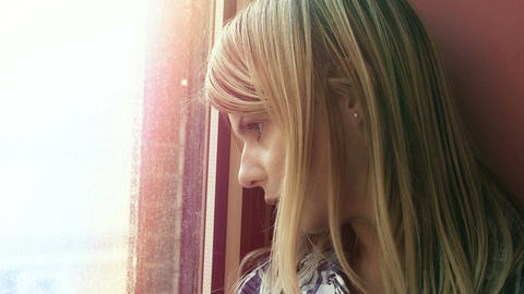hopeless young woman lost in her thoughts: sad woman looks out her window Footage