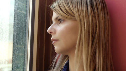 hopeless young woman looking out her window: depression, sadness Footage