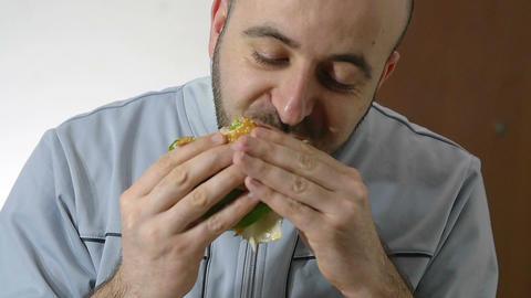 young man eating junk food: hamburger Live Action