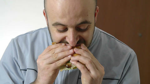 slow motion footage showing a man eating an hamburger Footage