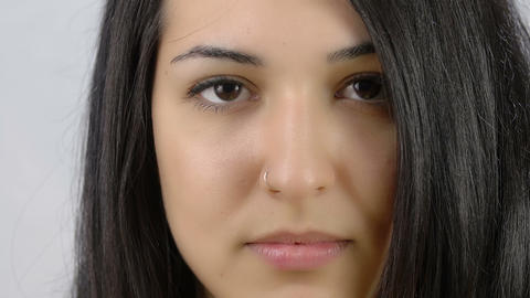 young pensive woman smiles in camera: beautiful woman closeup portrait Footage