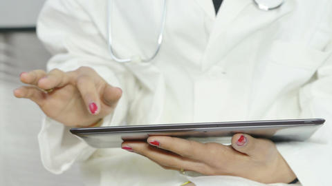 young female doctor using a tablet computer at work Footage