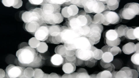 Big and Dark Bokeh of the Sun Glares Reflected From Water Footage