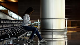 Woman stare to cellphone while sit in empty terminal lounge, texting to friends Footage