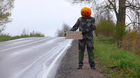 Man perform prank, stand with carton sign at roadside, ask why so serious Footage