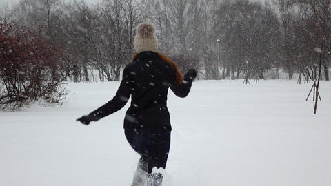 Woman happily run away on deep fluffy snow, snow flurry slow motion Footage
