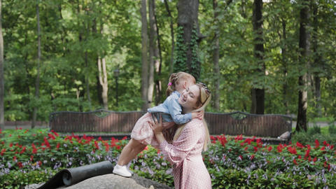 Happy young mother with little daughter having fun in the park Live Action