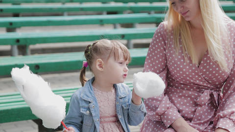 Beautiful and happy little girl eating cotton candy on the bench. Young happy Live Action