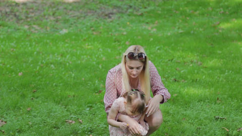 Young mother and little daughter are having fun in the park in sunny weather Live Action