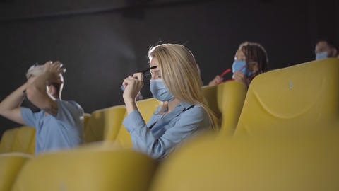 People watching movie in cinema on coronavirus pandemic. Angle view of men and Live Action