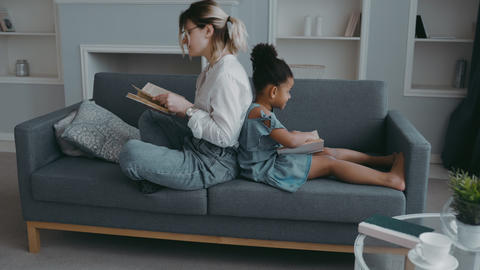 Mom and African daughter sit on sofa in modern living room back to back and read Live Action