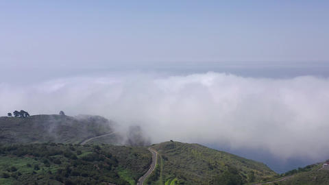Flight over the clouds and the surface of Tenerife. Mountain roads, villages and Live Action