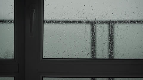Outside is raining and inside view of the window frame and glass. Close up of a Live Action