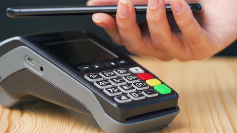 Contactless payment with smartphone. Wireless payment concept. Close-up, woman Live Action