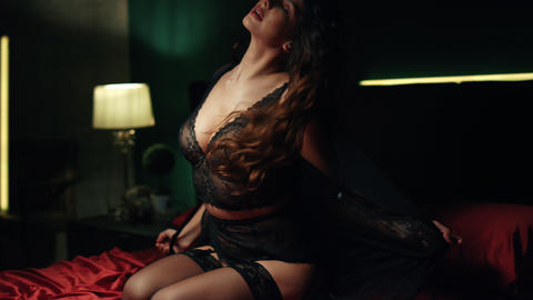 Sexy woman posing in red silk bed. Seductive girl kicking off lace peignoir Live Action