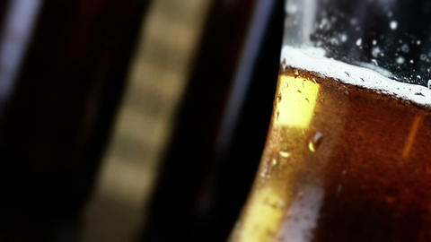 man drink fresh beer with foam in front of beer bottles background, beverage and relax in Live Action
