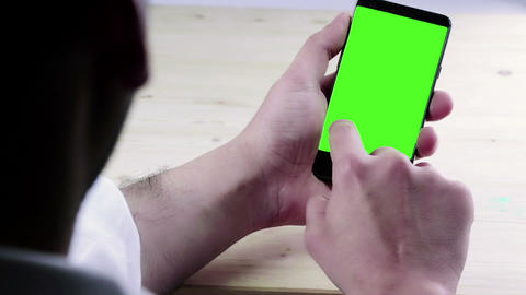 man hand using a smart phone with chroma key on wood table behind view, green screen, lifestyle Live Action