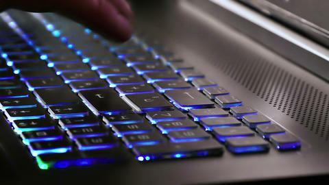 man typing on notebook keyboard with blue Live Action